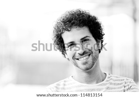 Portrait of attractive man with curly hairstyle smiling in urban background - stock photo