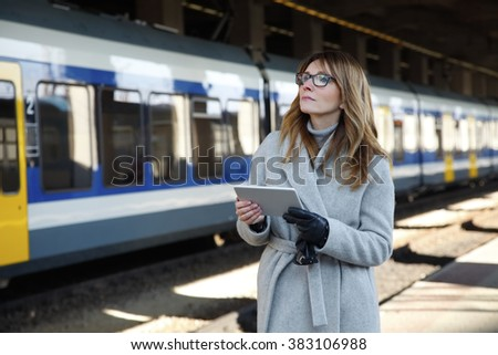 Portrait of attractive middle age businesswoman standing at railway platform at the station and using digital tablet to checking the timetable while waiting for the train. - stock photo