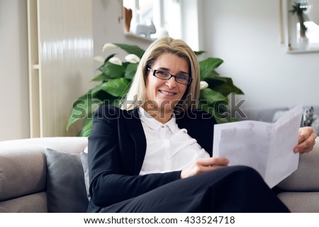 Portrait of attractive middle-aged business woman sitting on modern sofa at home and smiling into the camera. Confident woman with black suit reading white papers in bright living room. - stock photo