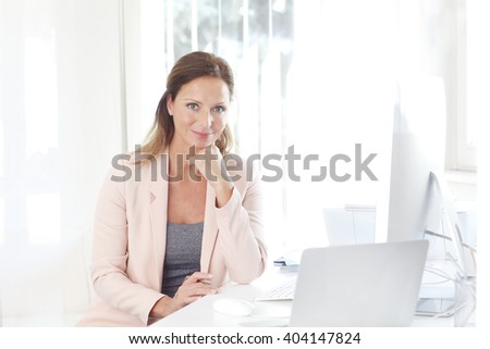 Portrait of attractive middle aged businesswoman sitting at her workplace in front of computer and laptop and working on new project. - stock photo