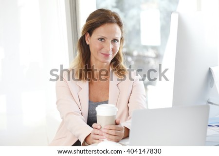 Portrait of attractive middle aged businesswoman sitting at her workplace in front of laptop and drinking coffee while working on new project.