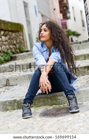 Portrait of attractive mixed woman in urban background wearing casual clothes - stock photo