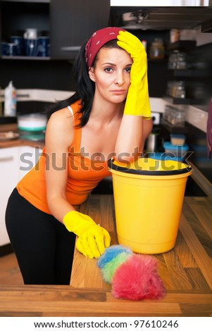 Portrait of attractive overworked  woman in kitchen - stock photo