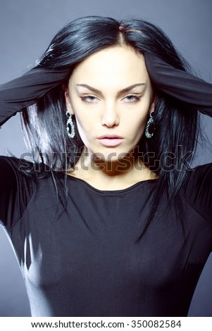 Portrait of attractive pretty sensual cool brunette young woman holding long black hair with hands in ear-rings and dress looking forward standing in studio on grey wall background, vertical picture