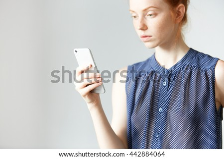 Portrait of attractive redhead girl in dot dress browsing the Internet on mobile phone. Pretty Caucasian woman typing a message or checking email using smart phone at home. Selective focus on the hand - stock photo