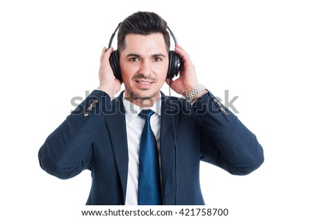 Portrait of attractive salesman with earphones listening music and smiling isolated on white background