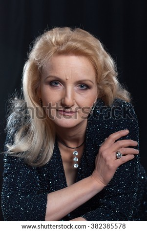 Portrait of attractive senior woman in a black dress at the black backgrounds