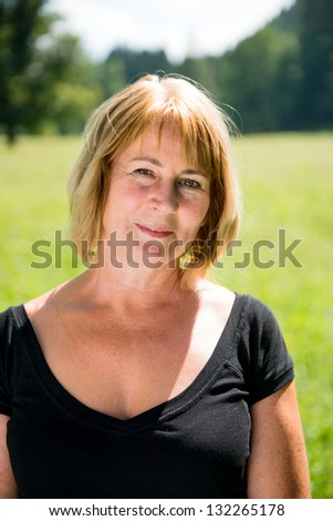 Portrait of attractive senior woman - outdoor on sunny day - stock photo