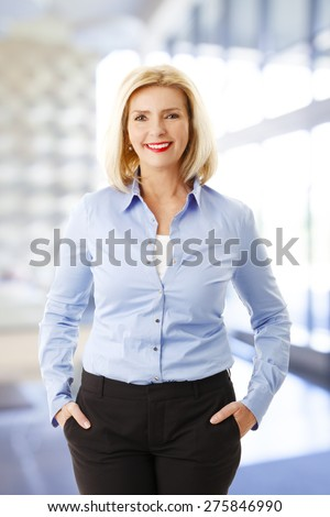 Portrait of attractive senior woman standing at room while looking at camera and smiling. - stock photo