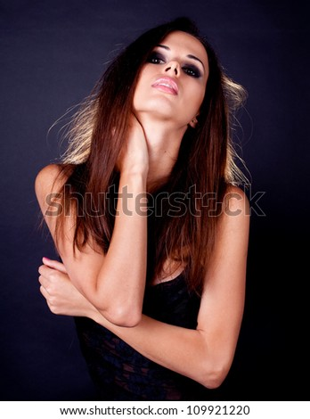 Portrait of attractive sexy young woman against dark background - stock photo