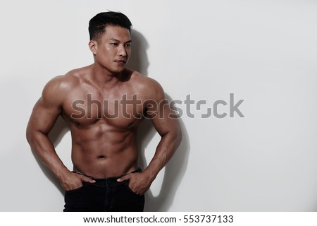 Portrait of attractive shirtless man standing against white wall