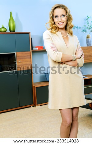 Portrait of attractive smart blond woman standing in living room. - stock photo