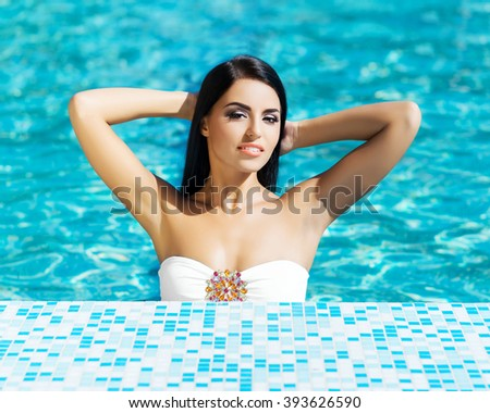 Portrait of attractive, smiling brunette having a recreation in the swimming pool. - stock photo