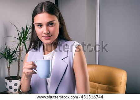 Portrait of attractive smiling brunette with cup of coffee in office - stock photo