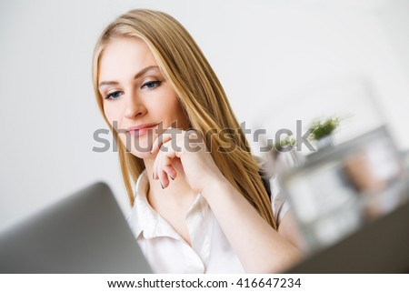 Portrait of attractive smiling caucasian businesswoman with hand at chin sitting at office desk with laptop and glass of water - stock photo