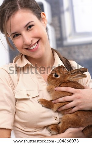 Portrait of attractive smiling girl cuddling with pet brown rabbit.
