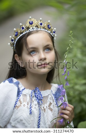 Portrait of attractive smiling princess girl with long brunette hair in traditional ukrainian embroidery white blue colors and beautiful diadem with diamonds in gold outdoor, vertical picture - stock photo