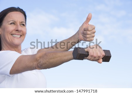 Portrait of attractive sporty mature woman in blurred background with thumbs up and stretched out arm with weight in focus, confident expression, healthy lifestyle, with blue sky as copy space. - stock photo