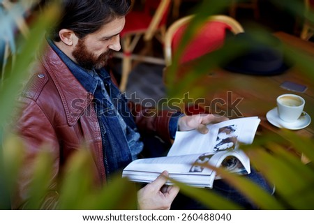 Portrait of attractive stylish man reading a magazine while drink coffee in coffee shop  - stock photo