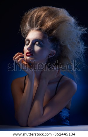 Portrait of Attractive stylish woman with messy hair posing on blue Background - stock photo