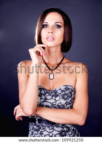 Portrait of attractive stylish young woman against dark background - stock photo
