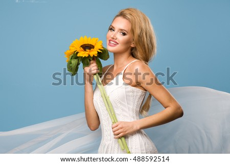 Portrait of attractive summer woman with sunflower in hand on blue background