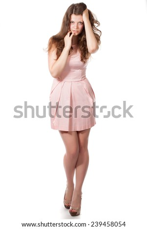 portrait of attractive surprised excited smile teenage girl in rose dress. Studio shot. Isolated on white background - stock photo