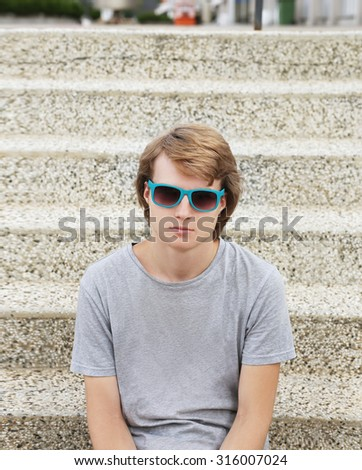 Portrait of attractive teenage boy sitting against grey background - stock photo