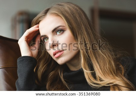 Portrait of attractive thoughtful young woman sitting at home - stock photo
