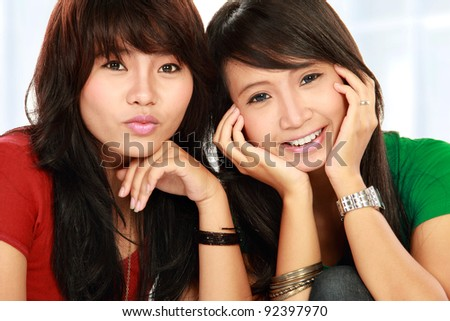portrait of attractive two girls smiling to the camera - stock photo