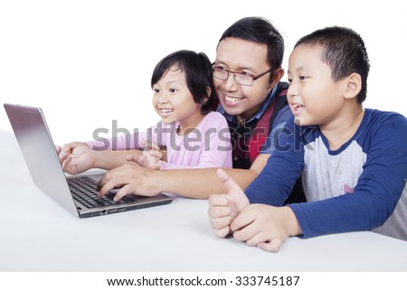Portrait of attractive two siblings and dad using laptop computer for surfing internet, isolated on white background