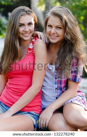 portrait of attractive two teen female girls women best friend having fun - stock photo