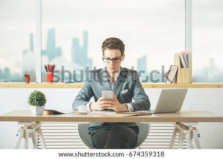 Portrait of attractive white man using smartphone while sitting at desk with laptop, coffee cup and other items in modern office with city view
