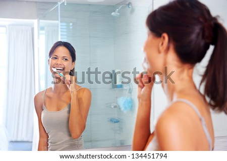 Portrait of attractive woman brushing teeth in bathroom and looking in the mirror at reflection. healthy teeth. - stock photo