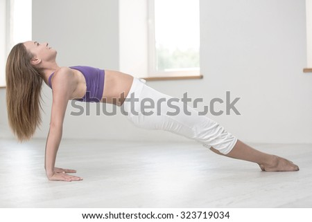 Portrait of attractive woman doing yoga exercises in gym