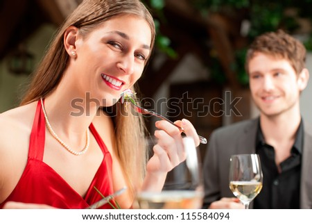 Portrait of attractive woman eating food with boyfriend sitting in background