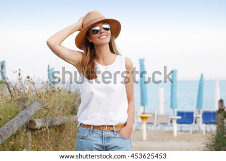 Portrait of attractive woman enjoying summer day by the sea.