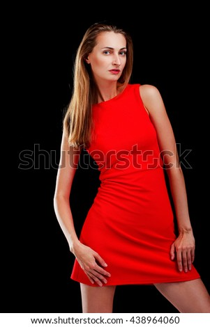 Portrait of attractive woman in red dress on black - stock photo
