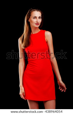 Portrait of attractive woman in red dress on black background - stock photo