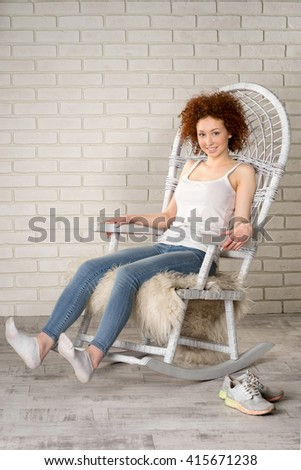 Portrait of attractive woman in rocking-chair - stock photo
