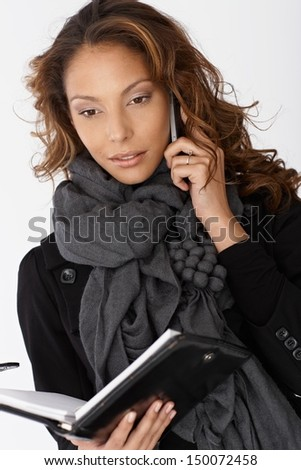 Portrait of attractive woman in scarf with mobile and personal organizer.