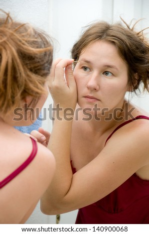 portrait of attractive  woman making her make-up - stock photo
