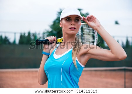 Portrait of attractive woman playing in tennis outdoors