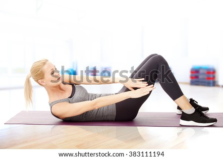 Portrait of attractive woman sitting at pilates mat and doing sit ups at the gym. - stock photo