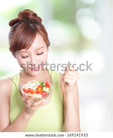 portrait of attractive woman smile eating salad isolated on green background, asian beauty model - stock photo