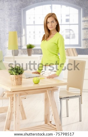 Portrait of attractive woman standing in living room by table, looking at camera.?