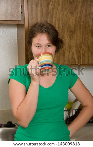 portrait of attractive woman with cup of tea in a kitchen - stock photo