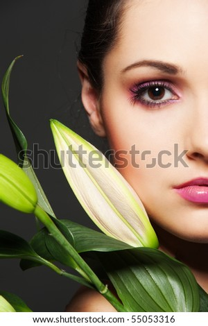 portrait of attractive woman with green flower over dark background - stock photo