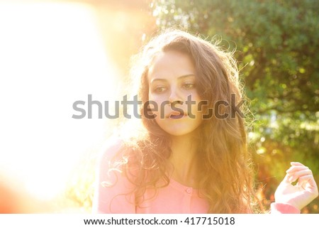 Portrait of attractive woman with long hair outside in bright sunlight