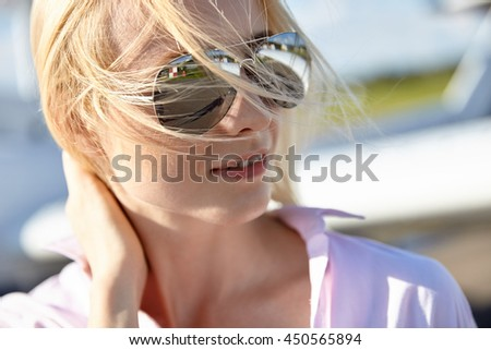 Portrait of attractive young adult blond girl in sunglasses posing at the air craft.  - stock photo